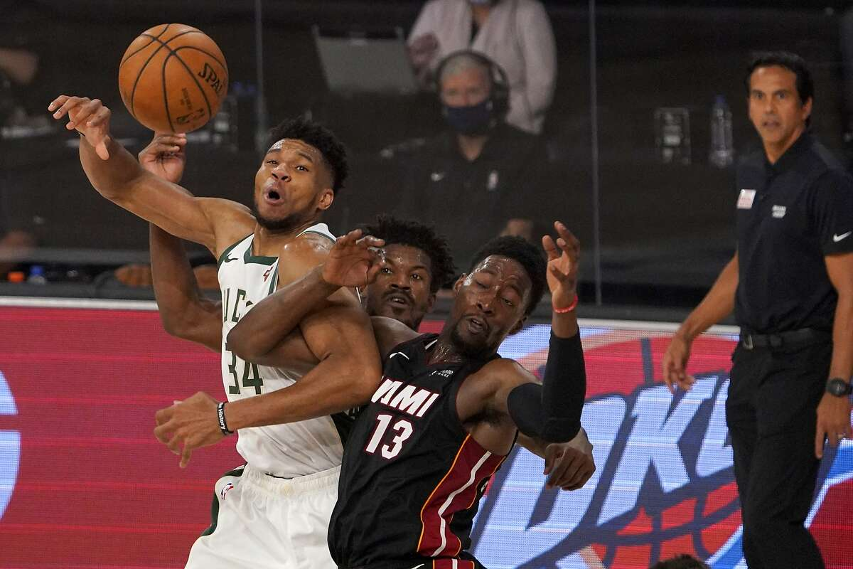 Milwaukee Bucks' Giannis Antetokounmpo (34) loses control of the ball as Miami Heat's Bam Adebayo (13) and Jimmy Butler, rear, defend during the second half of an NBA basketball conference semifinal playoff game, Monday, Aug. 31, 2020, in Lake Buena Vista, Fla. The Heat's Erik Spoelstra, right, looks on during the play. (AP Photo/Mark J. Terrill)