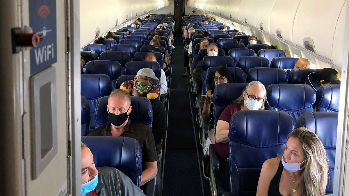 Masked passengers fill a Southwest Airlines flight from Burbank, Calif., to Las Vegas on June 3, 2020, with middle seats left open.