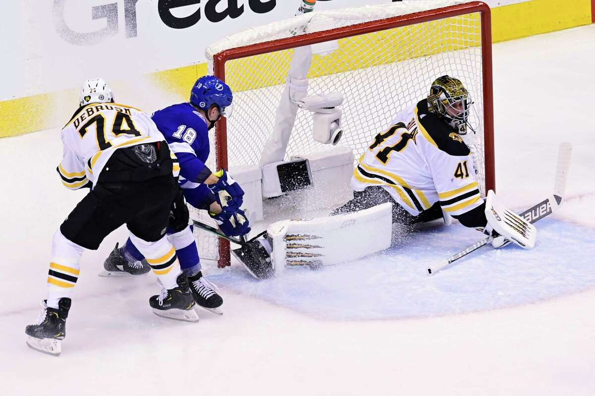 Boston Bruins goaltender Jaroslav Halak (41) stretches to make a save against Tampa Bay Lightning left wing Ondrej Palat (18) as Bruins left wing Jake DeBrusk (74) defends during first-period NHL Stanley Cup Eastern Conference playoff hockey game action in Toronto, Monday, Aug. 31, 2020. (Frank Gunn/The Canadian Press via AP)