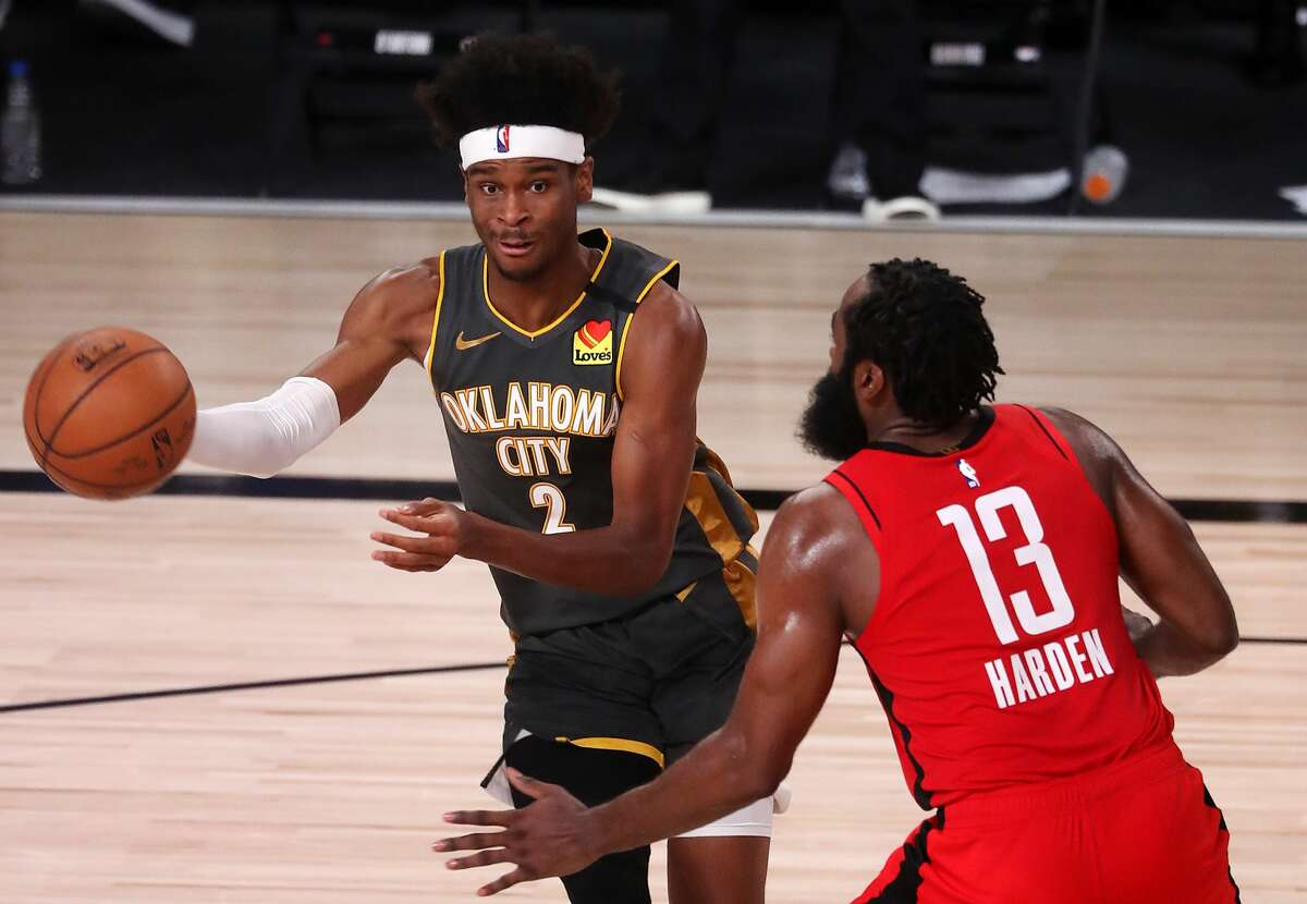 LAKE BUENA VISTA, FLORIDA - AUGUST 31: Shai Gilgeous-Alexander #2 of the Oklahoma City Thunder drives the ball against James Harden #13 of the Houston Rockets during the fourth quarter in Game Six of the Western Conference First Round during the 2020 NBA Playoffs at AdventHealth Arena at ESPN Wide World Of Sports Complex on August 31, 2020 in Lake Buena Vista, Florida. NOTE TO USER: User expressly acknowledges and agrees that, by downloading and or using this photograph, User is consenting to the terms and conditions of the Getty Images License Agreement. (Photo by Mike Ehrmann/Getty Images)