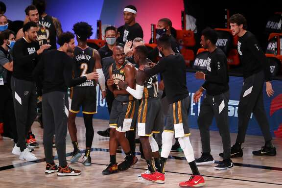 LAKE BUENA VISTA, FLORIDA - AUGUST 31: Chris Paul #3 of the Oklahoma City Thunder and Dennis Schroder #17 of the Oklahoma City Thunder celebrate their win with teammates against the Houston Rockets in Game Six of the Western Conference First Round during the 2020 NBA Playoffs at AdventHealth Arena at ESPN Wide World Of Sports Complex on August 31, 2020 in Lake Buena Vista, Florida. NOTE TO USER: User expressly acknowledges and agrees that, by downloading and or using this photograph, User is consenting to the terms and conditions of the Getty Images License Agreement. (Photo by Mike Ehrmann/Getty Images)