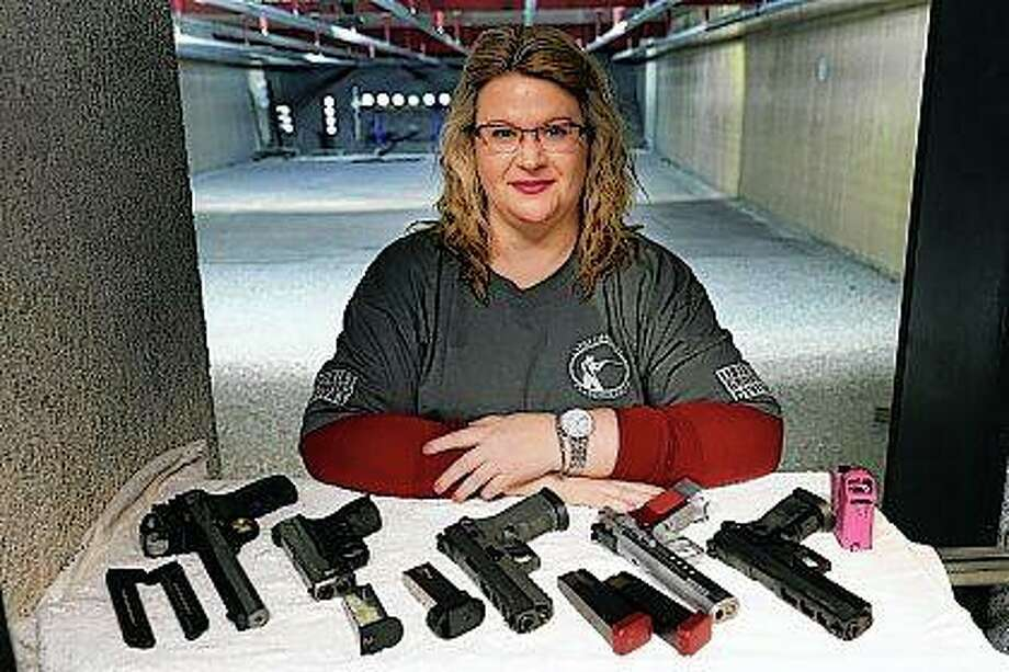 Kat Ellsworth poses in February at Caliber Tactical Gun Range in Waukegan for a portrait with five of the seven guns she owns. Americans' views are starkly different, underscoring the ever-widening divide over gun rights. Some call these gun-toting civilians patriots seeking to bring law and order in these turbulent times while others view them as vigilantes. Ellsworth, who heads the Liberal Gun Owners club in Illinois and who lives in Chicago, is appalled by those who have converged on protests and are openly carrying firearms. Photo: Charles Rex Arbogast | Associated Press