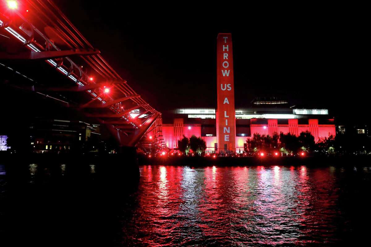 The Tate Modern in London is lit up in red as supporters also shine red lights from the Millennium Bridge as part of the #WeMakeEvents'