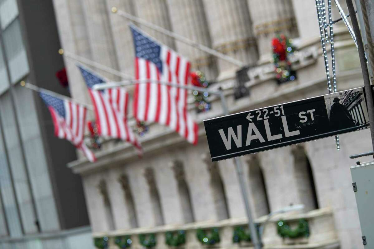 In this Jan. 3, 2020 file photo, the Wall St. street sign is framed by American flags flying outside the New York Stock Exchange in New York.