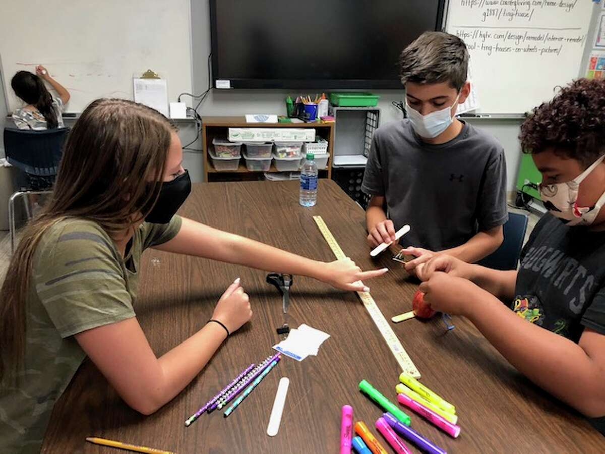 Kerri Latham, who teaches a gifted and talented class at Brooks Middle School, is working with Olivia Agee, from left, Aidan McClure and E.J. Rosette.