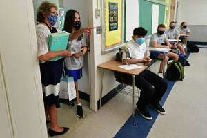 All Saints Catholic School eighth-grade teacher Patricia Hauptman greets her students as they attend their first day of class, Tuesday, September 1, 2020, in Norwalk, Conn. The school staggered its opening this year with grades six through eight attending Tuesday.