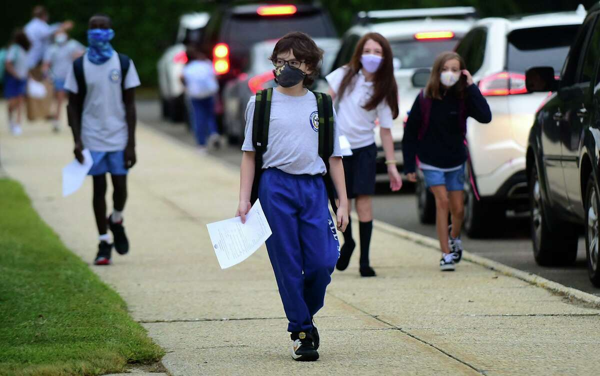 All Saints Catholic School students arrive for their first day of class with daily medical forms in hand, Tuesday, September 1, 2020, in Norwalk, Conn. The school staggered its opening this year with grades six through eight attending Tuesday.