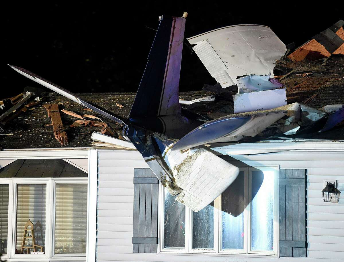 A plane is seen smashed into the roof of a home following a crash late Monday evening, Aug. 17, 2020, in Groton, Conn. The small plane crashed into the home while en route to a local airport Monday night, but the pilot, a passenger and a man in the house escaped serious jury, state and local officials said. (Sarah Gordon/The Day via AP)