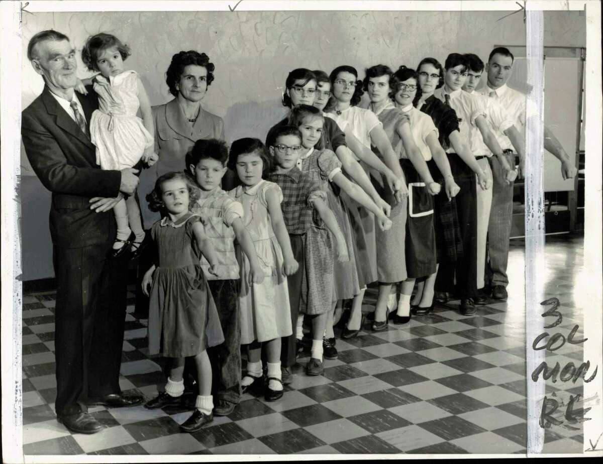 Families-large - Responding to plea of the Mothers' March on Polio, the nation's largest family turns out en masse for anti-polio vaccine injections. Baring their arms are Mr. and Mrs. Elmer de Golier of Brocton, New York, and their 20 children. Mr. de Golier holds Janeen, three, and his wife stands next to him. Children are (left to right) Valerie, five; Reed, six; Charlene, seven; Keith, 10; Sharon, 11; Sheila, 13; Rozella, 16; Ardys, 17; Theora, 20; Gloria Lee, 24; Joyce, 28, Carl, 14; Warren, 19 and Dexter, 27. Children not present are Wanda, 19; Dennis, 21; Joan, 23; Beverly, 25, and Gordon, 26.