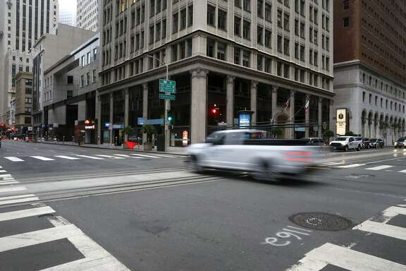 A vehicle rolls through the deserted intersection of California and Battery streets during the morning commute in San Francisco, Calif. on Tuesday, Aug. 25, 2020. Some businesses have remained open despite few office workers and commuters populating the Financial District during the coronavirus shutdown.
