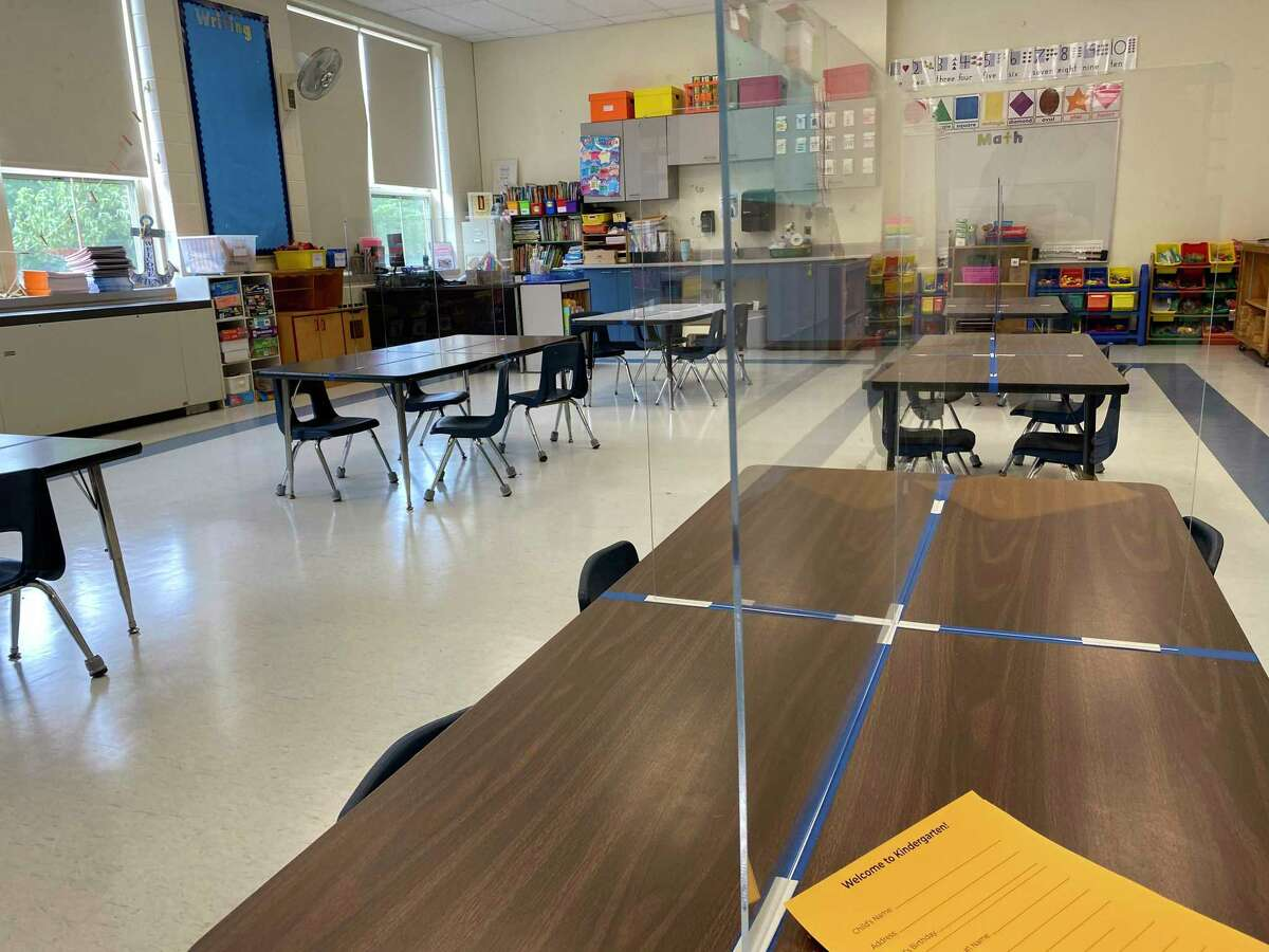 Royle School is preparing for Darien's first day of school. A kindergarten classroom has tables divided by plexiglass.