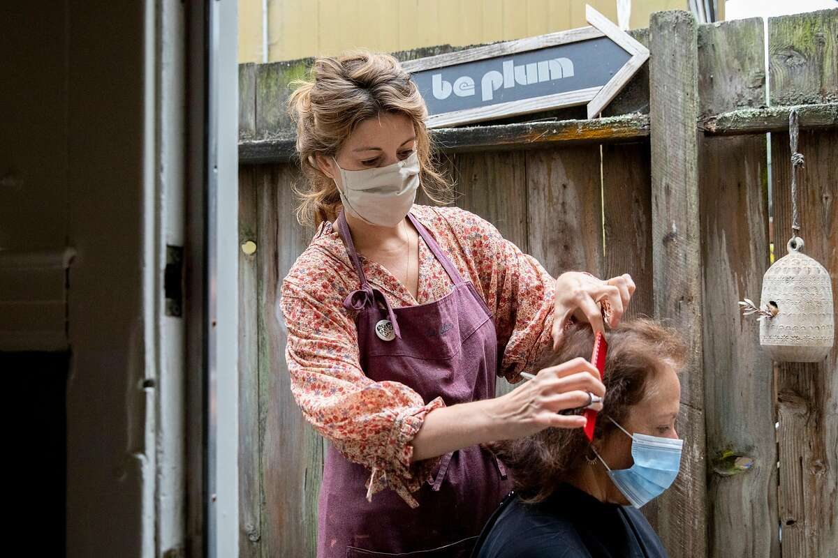 Plum Organic Beauty owner Danica Winters cut Martha Gregg's hair in the outdoor patio of her salon in San Francisco, Calif. Tuesday, September 1, 2020. Massage, hair and nail salons in San Francisco are permitted to open outdoors starting Tuesday, September 1 for the first time since COVID-19 shelter-in-place orders shuttered most personal service businesses.