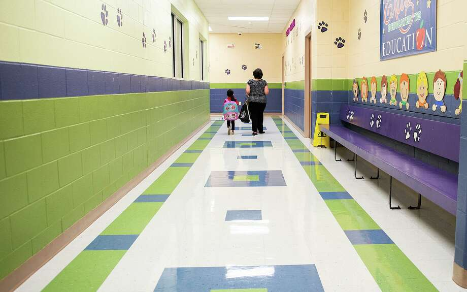 M.S. Ryan Elementary School paraprofessional Araceli Arredondo, right, escorts a student down a normally busy hall towards the cafeteria on Aug. 24 during the first day back to school for some students during the COVID-19 pandemic. Photo: Danny Zaragoza / Laredo Morning Times
