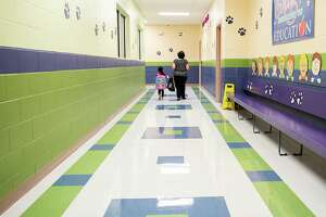 M.S. Ryan Elementary School paraprofessional Araceli Arredondo, right, escorts a student down a normally busy hall towards the cafeteria on Aug. 24 during the first day back to school for some students during the COVID-19 pandemic.