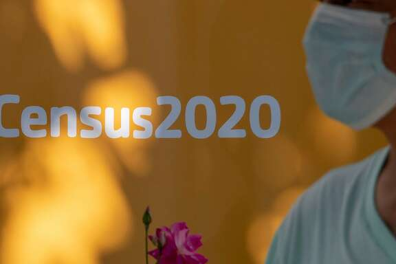 A man wearing a facemask walks past a sign encouraging people to complete the 2020 US Census, in Los Angeles, California, August 10, 2020 amid the COVID-19 pandemic. - The result of the Census, which the Census Bureau announced it would end one month early, on September 30, directly affects the amount of funding a community receives for services including public schools, hospitals and fire departments. (Photo by Robyn Beck / AFP) (Photo by ROBYN BECK/AFP via Getty Images)
