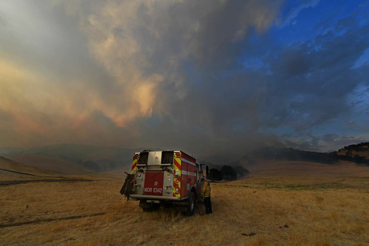 A firefighter crew keeps a watchful eye as spot fires burn on a hillside caused by a lightning strike along Marsh Creek Road in Brentwood, Calif., on Monday, Aug. 17, 2020.