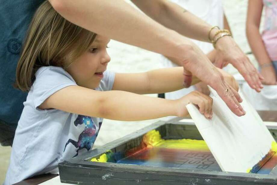 A student gets help with screen printing during a 2019 summer art class at Jacoby Arts Center, where 25 different art, dance and theater classes are being offered this fall for varying age groups.