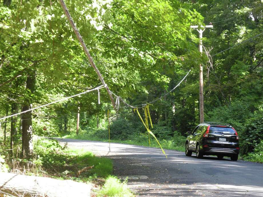A car passes under a low-hanging wire Hickory Hill Road on Aug. 30, the result of Tropical Storm Isaias that hit a month ago. Photo: Jeannette Ross / Hearst Connecticut Media / Wilton Bulletin