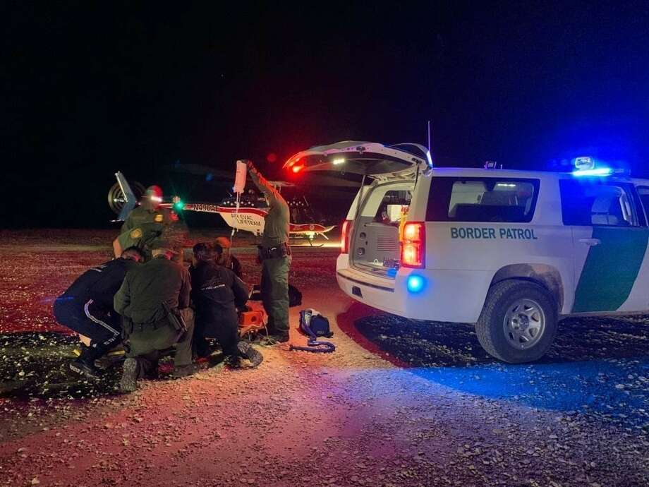 U.S. Border Patrol patrol agents are seen rendering aid to a woman who was abandoned by smugglers. Photo: Courtesy