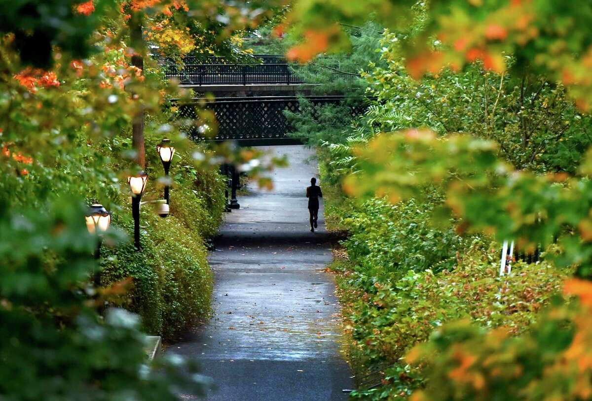 A jogger runs past fall foliage and in between rain drops along the Farmington Canal Trail near Trumbull Street, Prospect Street and Canal Street in New Haven.