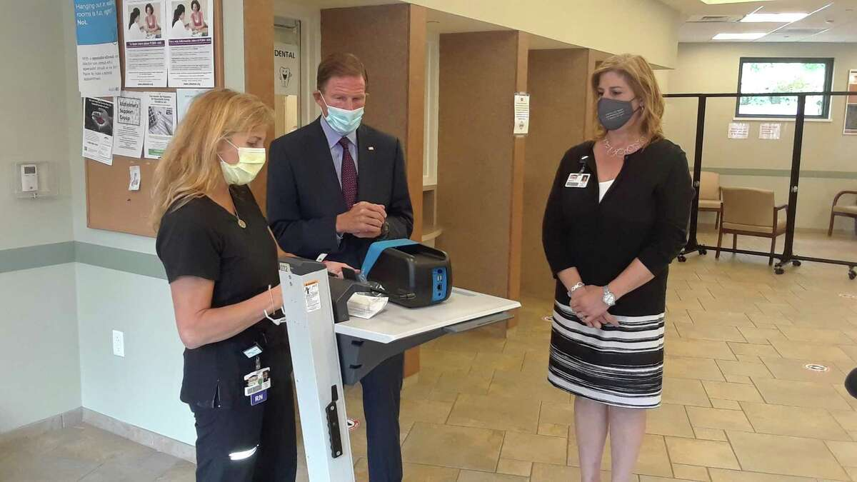 Sen. Richard Blumenthal listens to head nurse Michelle Brady at Community Health & Wellness Center of Greater Torrington explain a new rapid testing machine for COVID-19, which provides results in 15 minutes instead of two or three days. Also pictured is Joanne Borduas, CHWC's CEO, right. Blumenthal visited the center Tuesday afternoon.