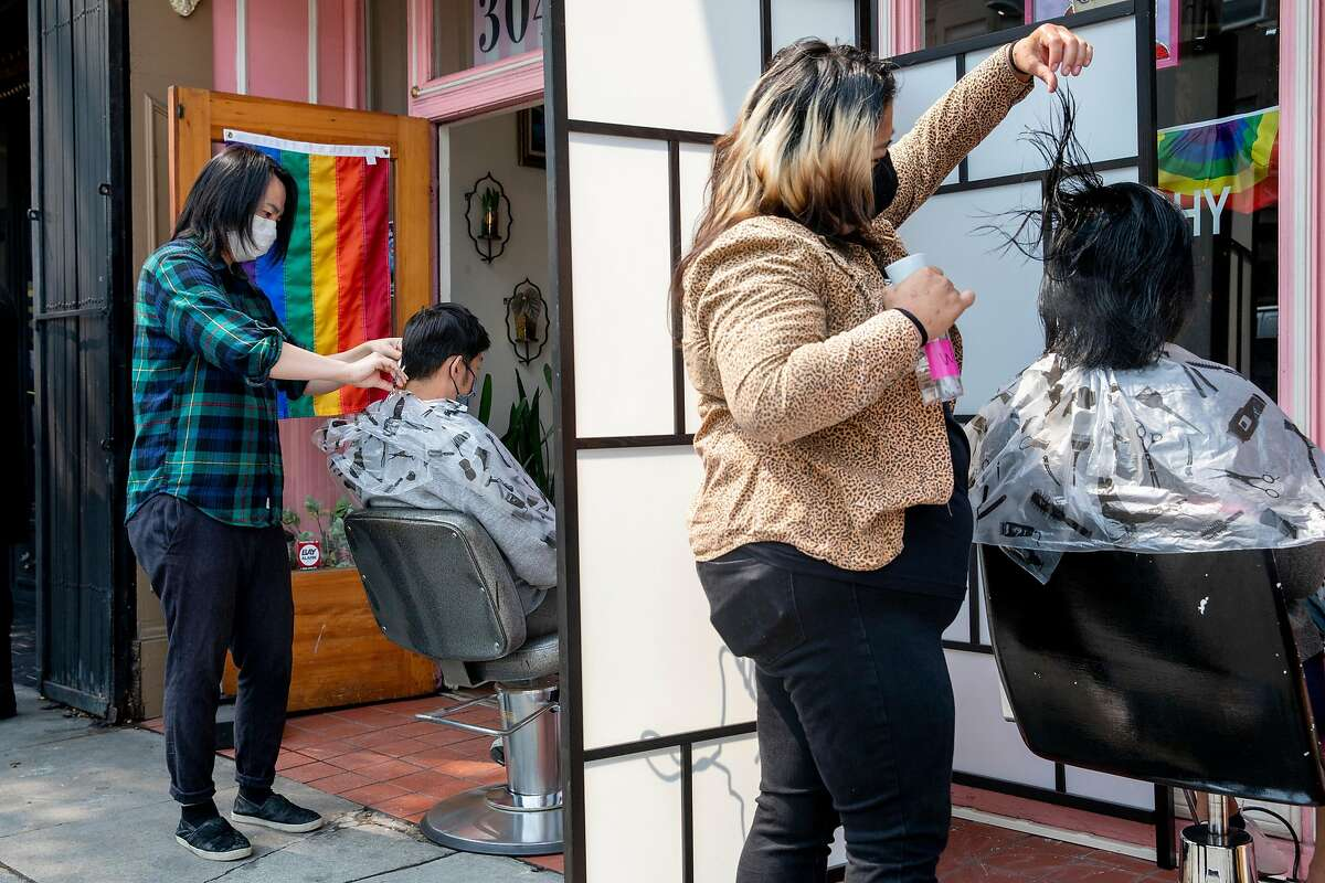 Hair stylists Masaaki Ino (left) and Lisette Liu-Maldonado (right) work to cut hair in an outdoor setting at Glama-Rama! Salon in San Francisco, Calif. Tuesday, September 1, 2020. Waxing, massage, hair and nail salons in San Francisco are permitted to open outdoors starting Tuesday, September 1 for the first time since COVID-19 shelter-in-place orders shuttered most personal service businesses.