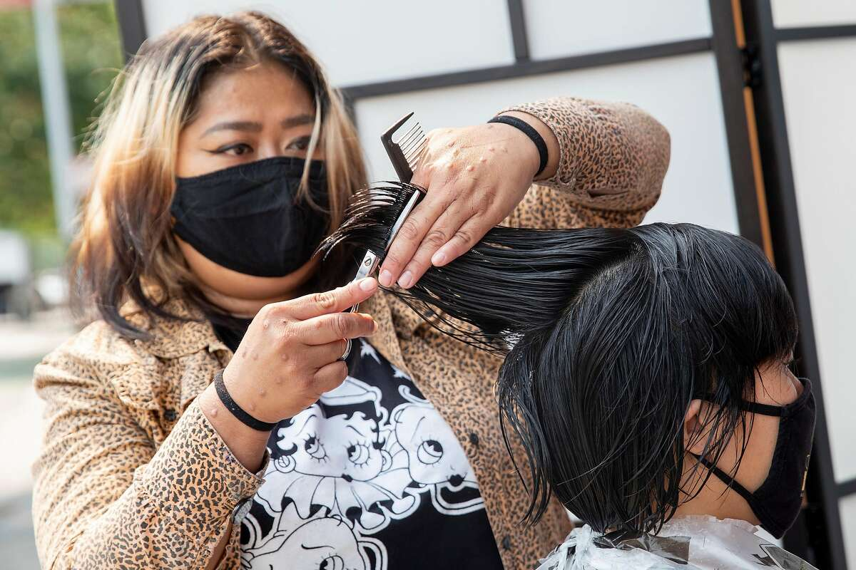 Hair stylist Lisette Liu-Maldonado wears a mask while cutting Connie Jew's hair in an outdoor setting at Glama-Rama! Salon in San Francisco, Calif. Tuesday, September 1, 2020. Waxing, massage, hair and nail salons in San Francisco are permitted to open outdoors starting Tuesday, September 1 for the first time since COVID-19 shelter-in-place orders shuttered most personal service businesses.