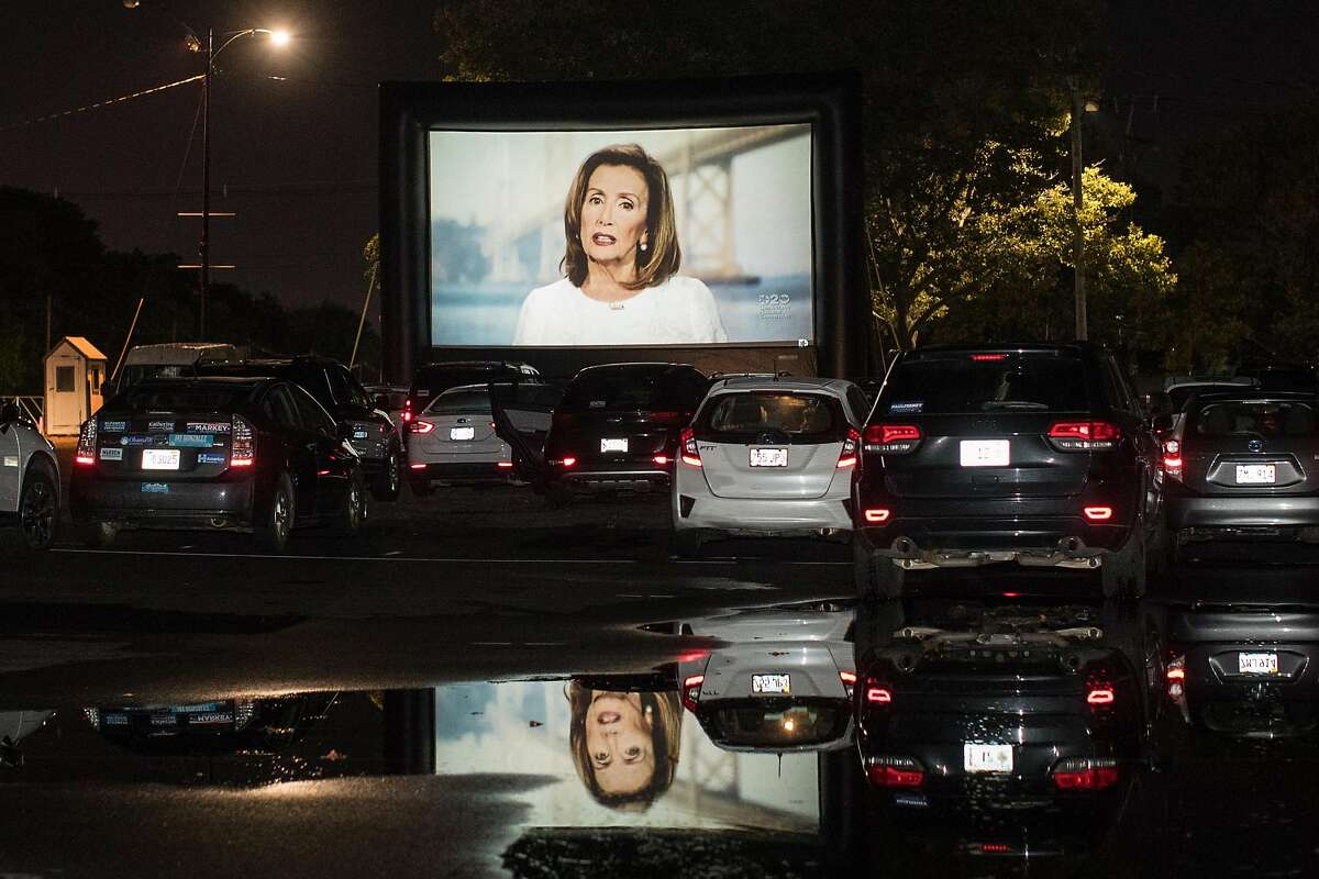 BOSTON, MA - AUGUST 19: A screen projects Speaker of the House Nancy Pelosi (D-CA) during a drive-in watch party for the virtual Democratic National Convention hosted by the Massachusetts Democrats at Suffolk Downs on August 19, 2020 in Boston, Massachus