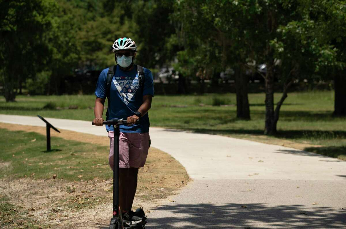 A man rides an electronic scooter with a mask on along the Brays Bayou Greenway Trail on June 18, 2020, at Hermann Park in Houston.
