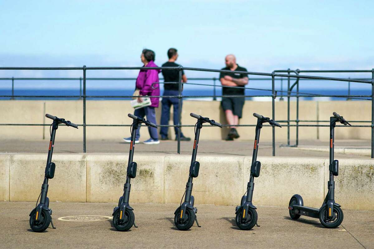 E-scooters sit parked on the promenade during a trial of rental e-scooters by Ginger Teleporter Ltd., in Redcar, U.K on Aug. 24, 2020. The U.K. has lagged the world in allowing e-scooters to operate legally on its roads, with some restrictive laws dating back to 1835.