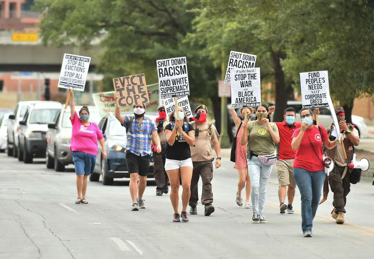 Marchers lead a caravan during a national day of protest against evictions, foreclosures, police brutality and racism recently in downtown San Antonio.
