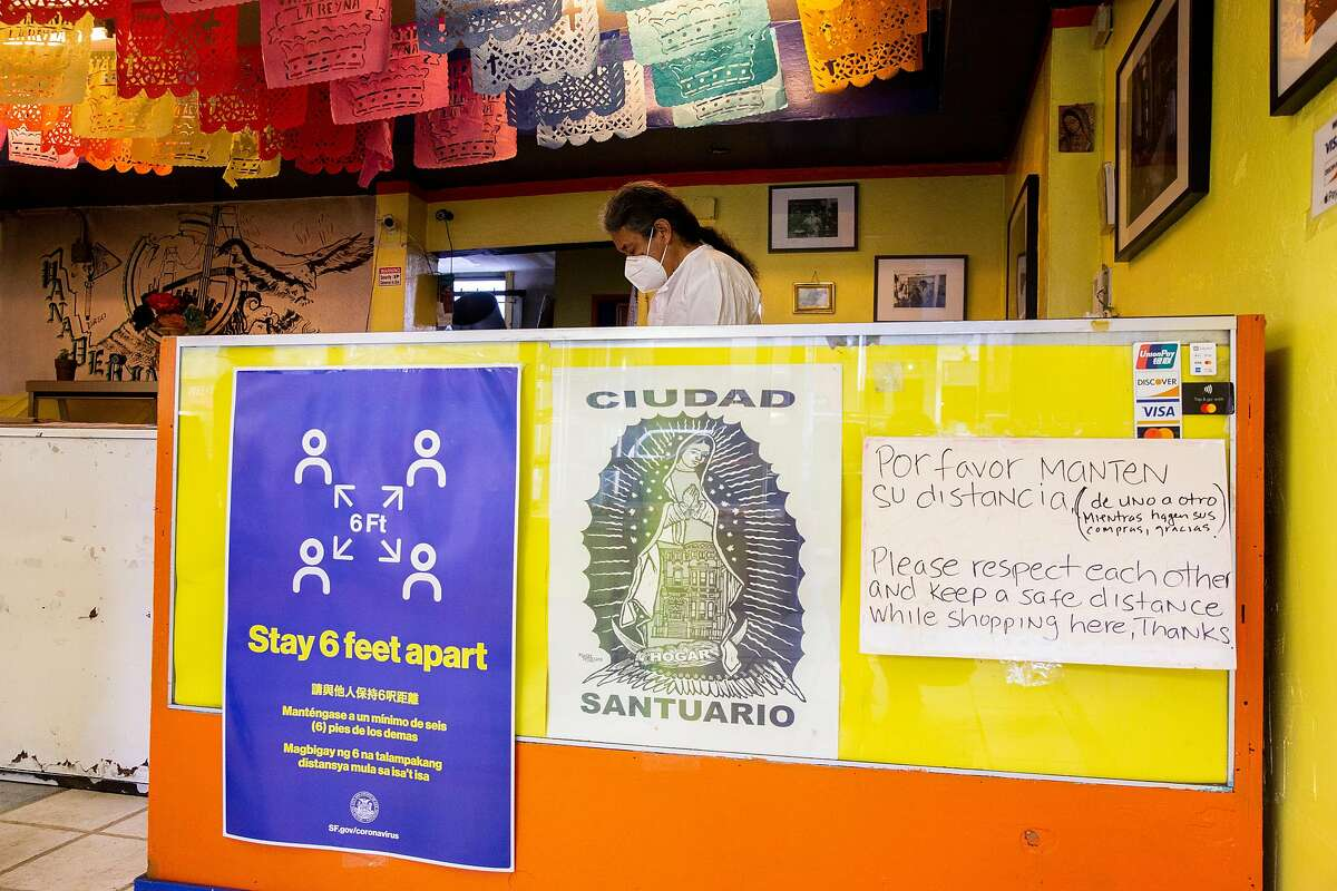 Luis Gutierrez waits for customers at La Reyna Bakery, Saturday, April 25, 2020, in San Francisco, Calif. Amid the coronavirus pandemic, businesses are taking precautious to help decrease the spread of the virus. He has signs in and out of his business displaying information on social distancing.
