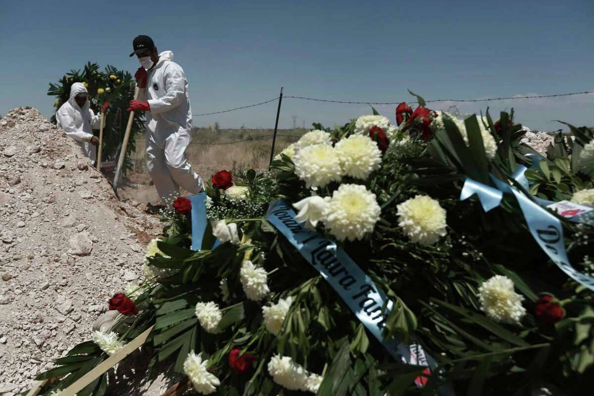Workers in full protection gear against the spread of the new coronavirus bury a coffin in an area of the San Rafael municipal cemetery that has been set apart for COVID-19 cases in Ciudad Juárez, Mexico. Labor activists believe that the working conditions are contributing to a rising mortality rate among factory workers in Mexico.