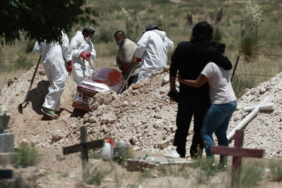 Family members mourn as workers bury their loved one in an area of a cemetery for COVID-19 cases in hard-hit Ciudad Juárez.