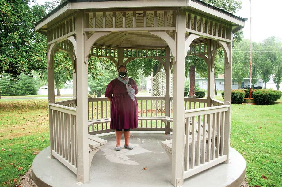 """Deloris """"DeDe"""" Summers takes shelter from the rain Tuesday in the newly gifted gazebo housed on the east side of the Illinois School for the Deaf. The gazebo — which is now vinyl and replaced an older wooden one — was gifted from the Illinois School for the Deaf Alumni Association. Photo: Darren Iozia 