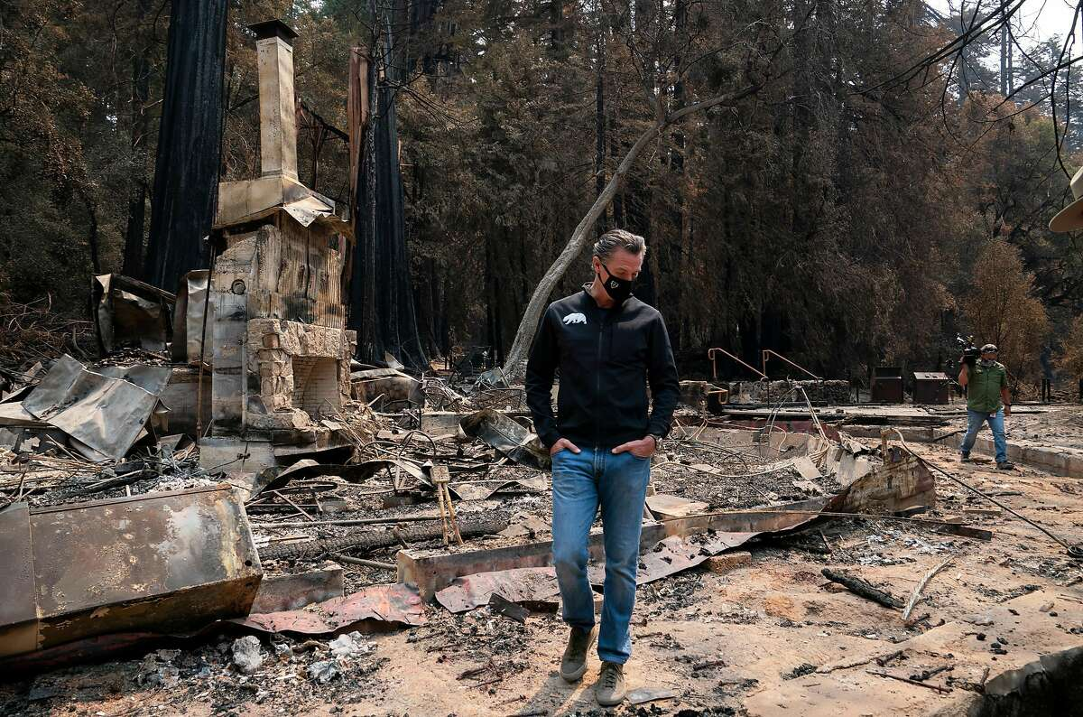 Governor Gavin Newsom walks through the remnants of the headquarters building as he tours the fire damage to Big Basin Redwoods State Park on Tuesday, Sept. 1, 2020 in Boulder Creek, Calif.