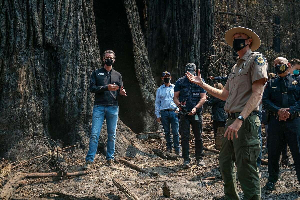 Governor Gavin Newsom, left, listens as Santa Cruz State Park Superintendent Chris Spohrer, right, talks about the fire damage to Big Basin Redwoods State Park on Tuesday, Sept. 1, 2020 in Boulder Creek, Calif.