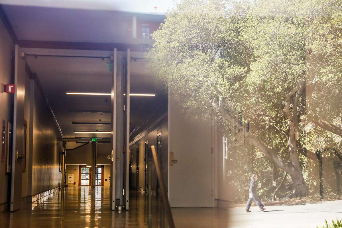 The empty hallway of Wheeler Hall is seen as a person is reflected in a window walking through the UC Berkeley campus on Wednesday, July 8, 2020 in Berkeley, California.