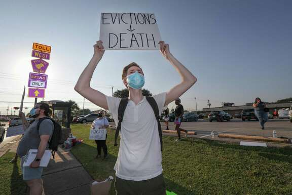 Ian Druke holds a sign during a protest regarding evictions going on at the court, 6000 Chimney Rock Rd., Friday, Aug. 21, 2020, in Houston.