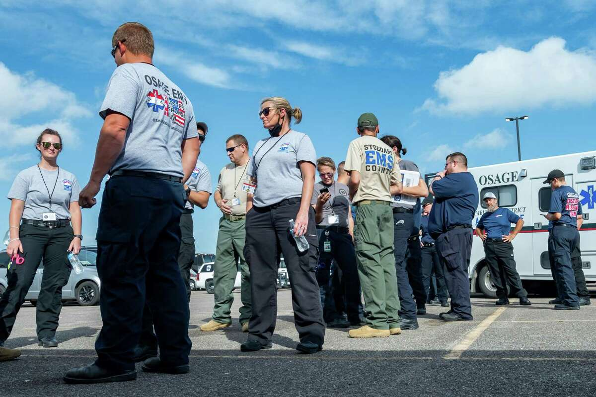 EMS personnel gather around the Southeast Texas Regional Advisory mobile command center to get their assignments. Before winds from Hurricane Laura begin picking up, more than 100 emergency vehicles staged at Ford Park. Photo made on August 26, 2020. Fran Ruchalski/The Enterprise