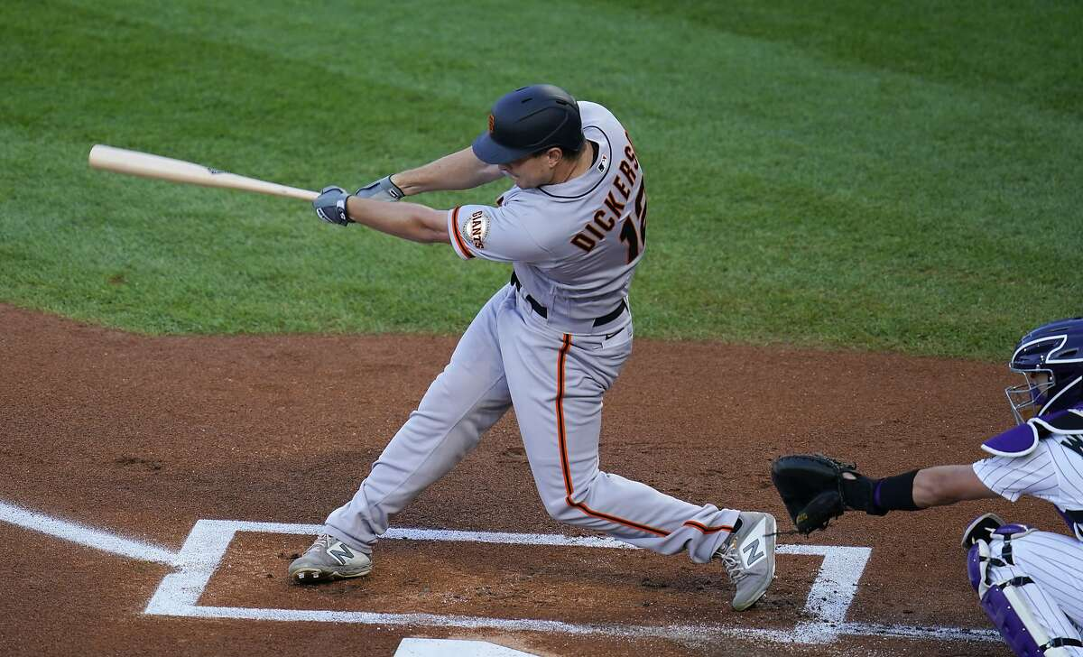 San Francisco Giants' Alex Dickerson connects for a solo home run off Colorado Rockies starting pitcher Jon Gray as catcher Tony Wolters looks for the pitch in the first inning of a baseball game Tuesday, Sept. 1, 2020, in Denver. (AP Photo/David Zalubowski)
