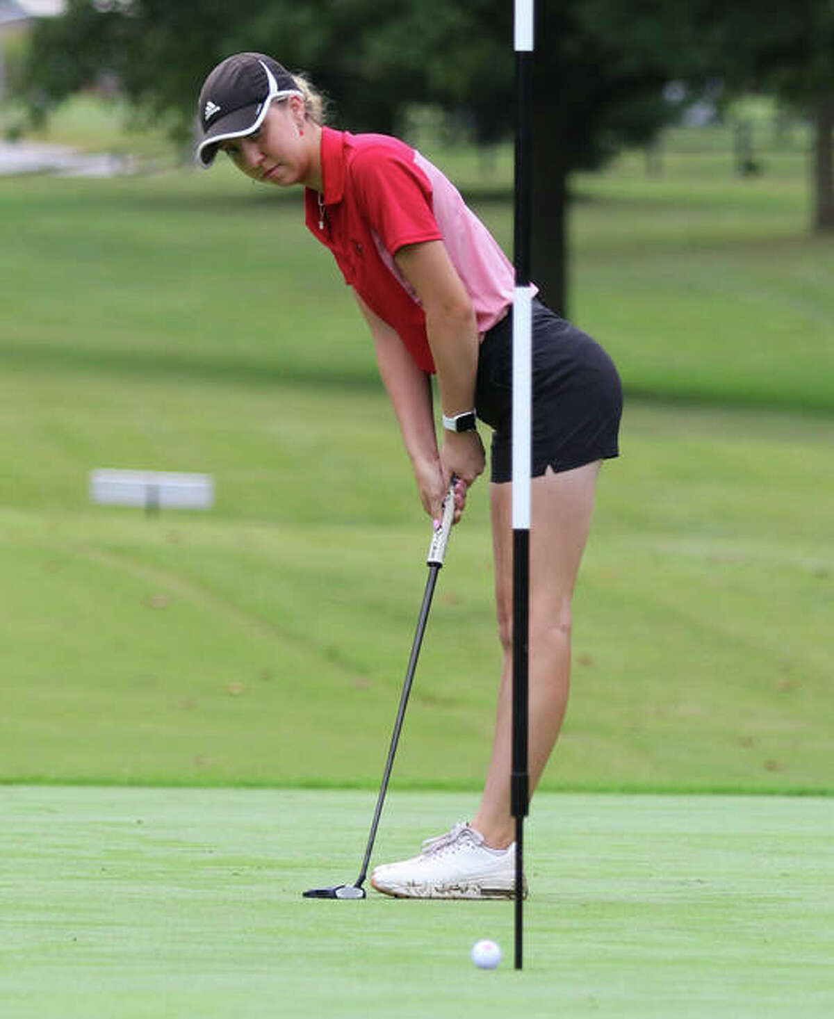 Alton's Natalie Messinger watches her putt roll into the cup to save par on the first hole Tuesday morning in the SWC Tourney at Belk Park Golf Course in Wood River. Messinger shot 72 to finish in a three-way tie for first.