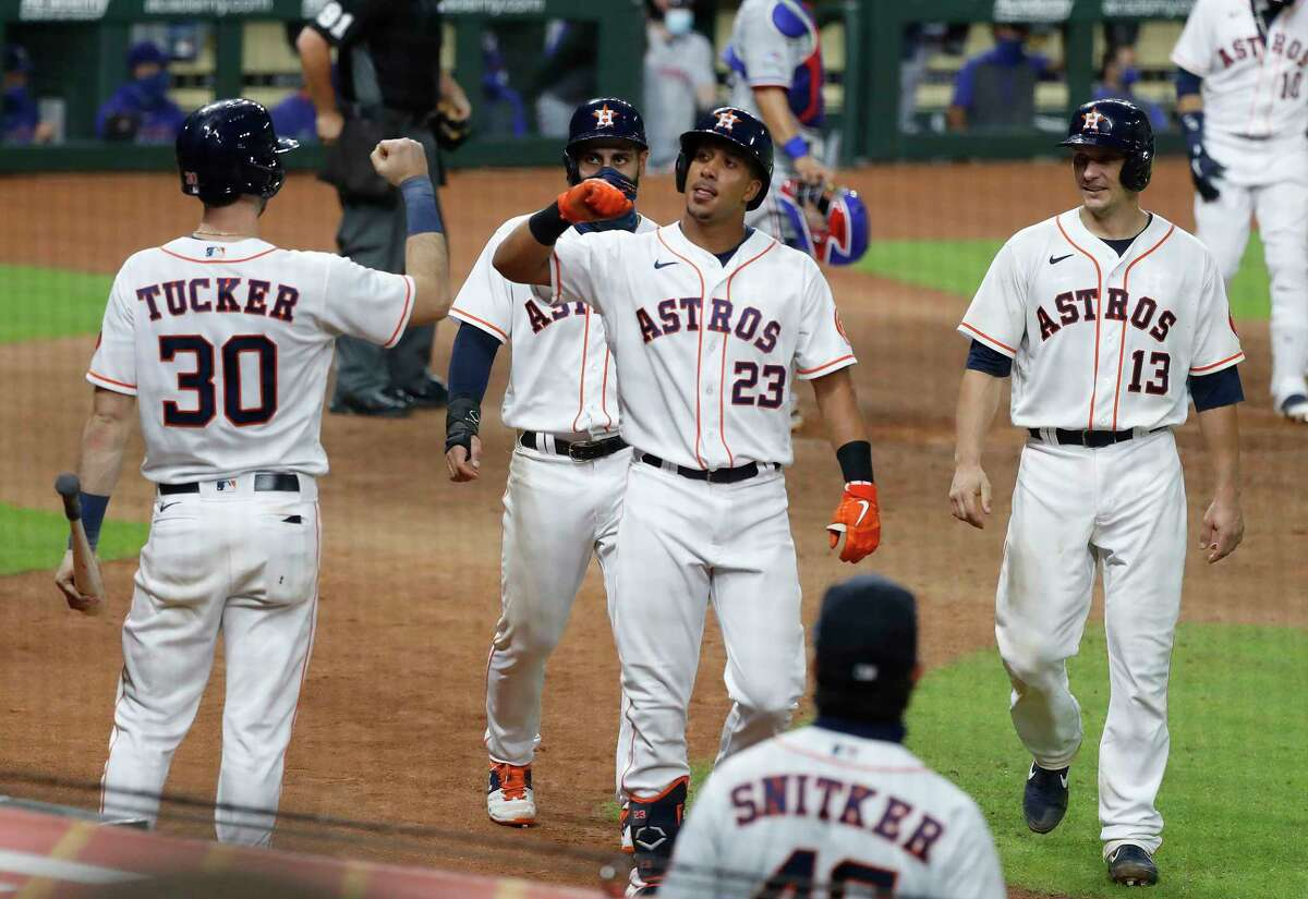 Houston Astros Michael Brantley (23) celebrates with Kyle Tucker (30) after he hit a three-run home run during the seventh inning of an MLB baseball game at Minute Maid Park, Tuesday, September 1, 2020, in Houston.
