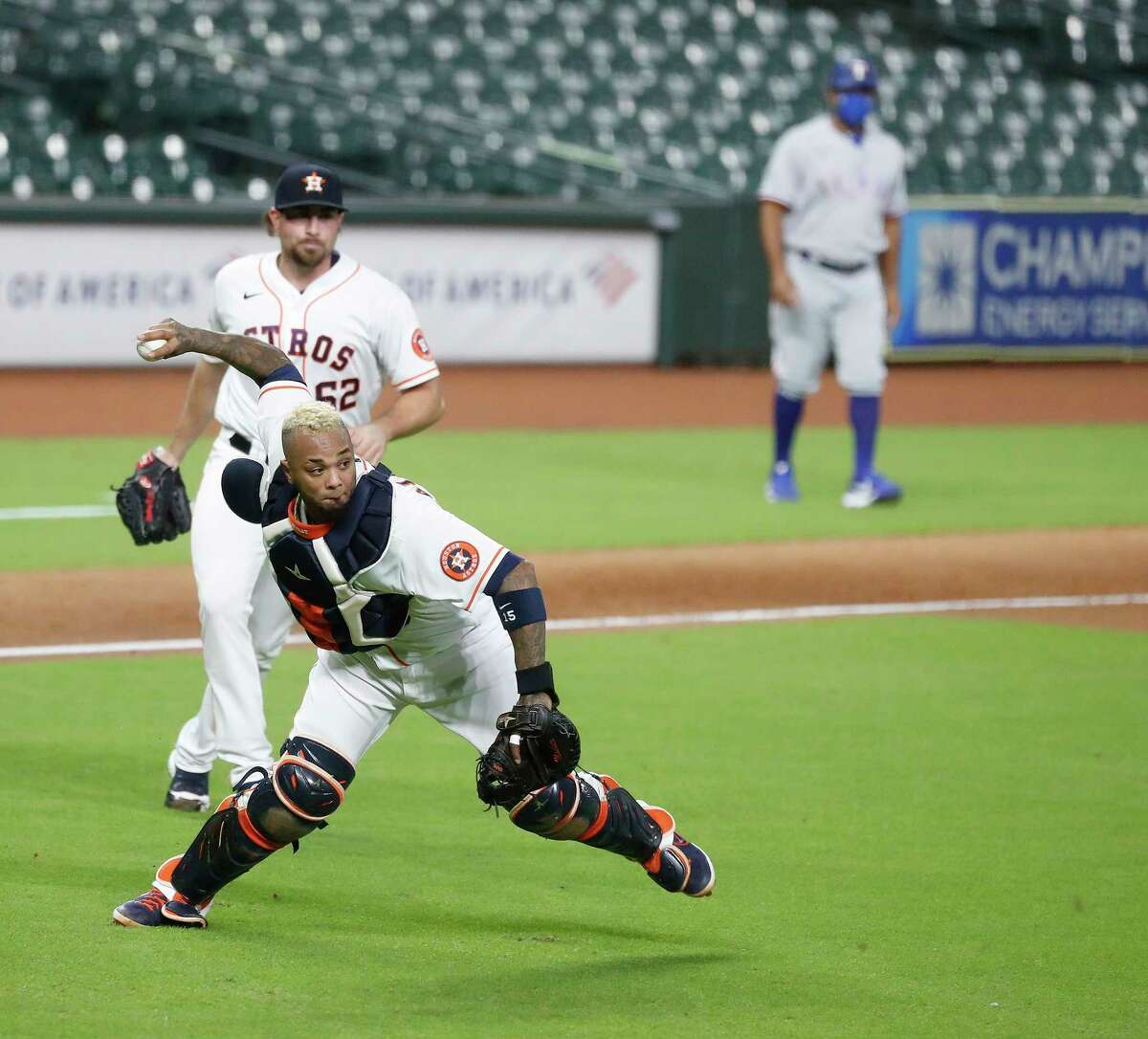 Houston Astros catcher Martin Maldonado (15) tries to make the throw to first base in an effort to get Texas Rangers right fielder Joey Gallo (13) out at first but he was able to advance and score a runner on the throwing error during the tenth inning of an MLB baseball game at Minute Maid Park, Tuesday, September 1, 2020, in Houston.