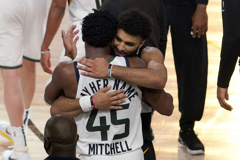 Utah Jazz's Donovan Mitchell (45) and Denver Nuggets' Jamal Murray, center rear, greet each other after their NBA first round playoff basketball game, Tuesday, Sept. 1,2020, in Lake Buena Vista, Fla. The Nuggets won 80-78. (AP Photo/Mark J. Terrill) Photo: Mark J. Terrill / Associated Press