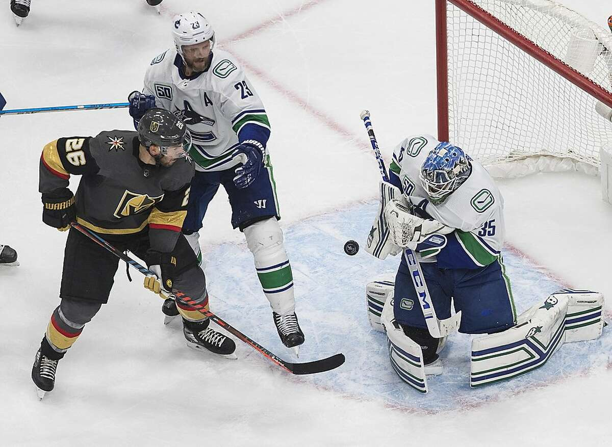 Vancouver Canucks goalie Thatcher Demko (35) makes a save as Vegas Golden Knights' Paul Stastny (26) and Canucks' Alexander Edler (23) look for a rebound during the third period of Game 5 of an NHL hockey second-round playoff series, Tuesday, Sept. 1, 2020, in Edmonton, Ontario. (Jason Franson/The Canadian Press via AP)