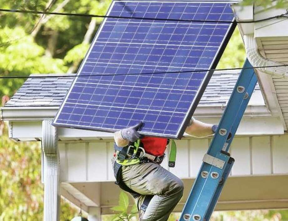 A worker carries a solar panel to the roof of a house in Godfrey in this 2016 file photo. Sixty projects are planned this year by Grow Solar Metro East and Grow Solar St. Louis programs, with another 60 households considering projects, according to Peter Murphy, Solar Program Director for the Midwest Renewable Energy Association. The group and Lewis and Clark Community College launched Grow Solar Metro East five years ago.