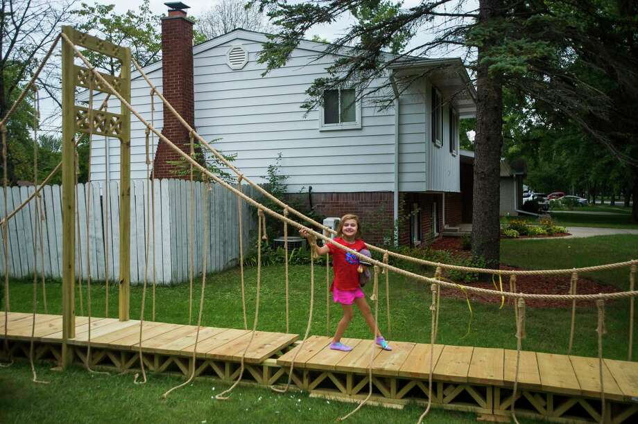 Mindy Sushynski, 5, walks across the 60-foot Mackinac Bridge replica built by her dad, Chris Sushynski, Tuesday, Sept. 1, 2020 in front of their home in Midland. (Katy Kildee/kkildee@mdn.net)