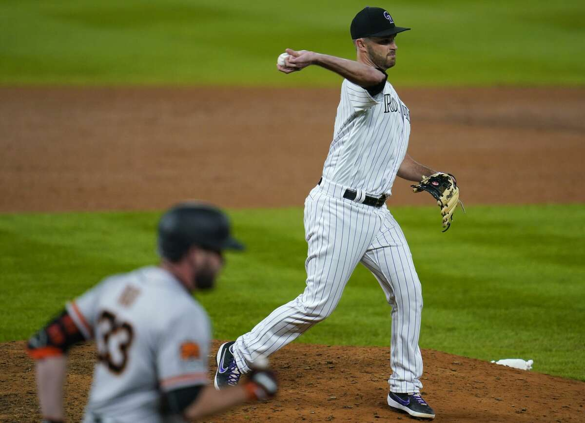 Colorado Rockies catcher Drew Butera, back, who took the mound to work as a relief pitcher, throws to first base to put out San Francisco Giants' Darin Ruf to end the top of the ninth inning of a baseball game Tuesday, Sept. 1, 2020, in Denver. The Giants won 23-5. (AP Photo/David Zalubowski)