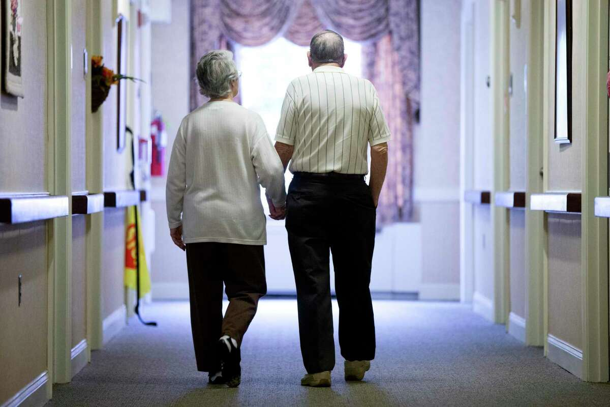 An elderly couple walks down a hall of a nursing home in Easton, Pa., in this archive picture.